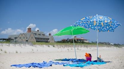 Parasoll på en sandstrand. Foto: John Minchillo/AP.