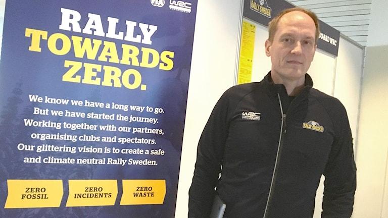 Glenn Olsson står vid sidan av en affisch med reklam för Rally Sweden. Foto: Jonas Berglund/Sveriges Radio.