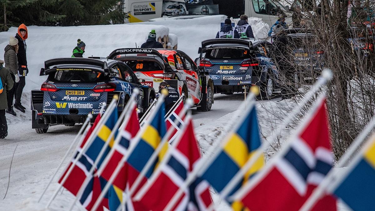 Bilar i en kö. I förgrunden norska och svenska flaggor. Foto: Isak Olsson/Sveriges Radio.