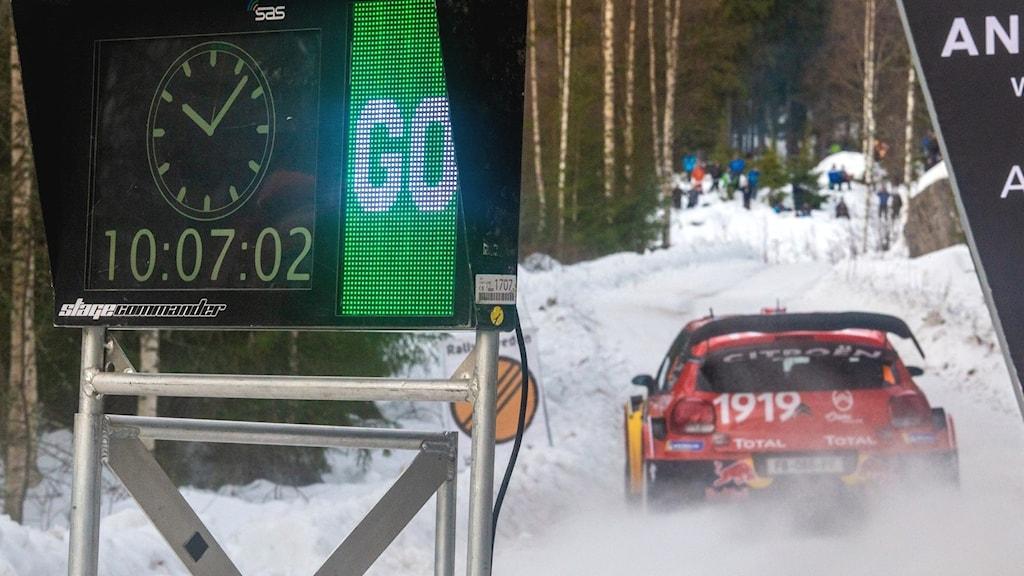 Ett tidtagarur och en rallybil. Foto: Isak Olsson/Sveriges Radio.