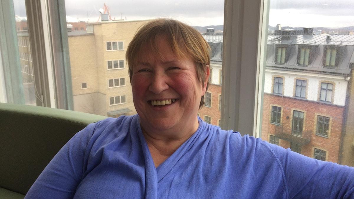 Eija Jurvelin hymyilee sininen asu päällään, taustalla kaupunkimnäkymä.