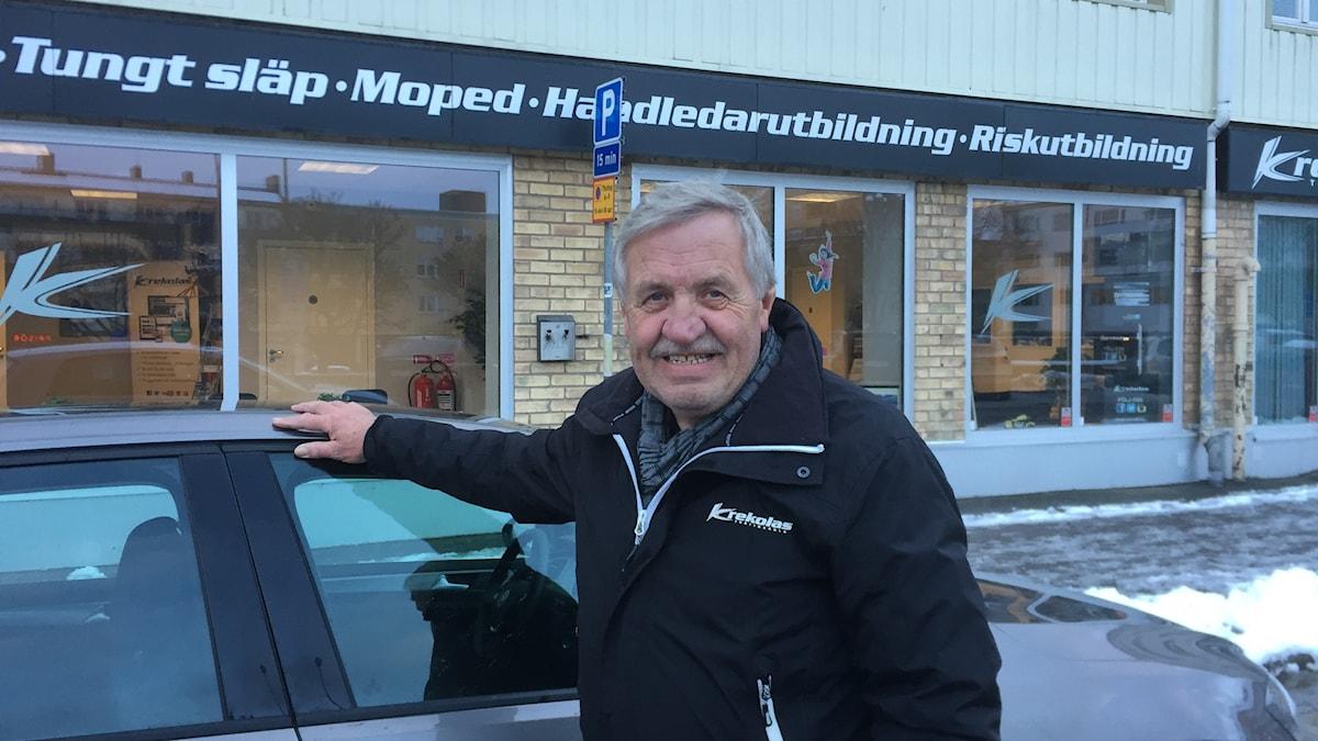 Juhani Krekola mustassa takissa nojaa auton kattoon.