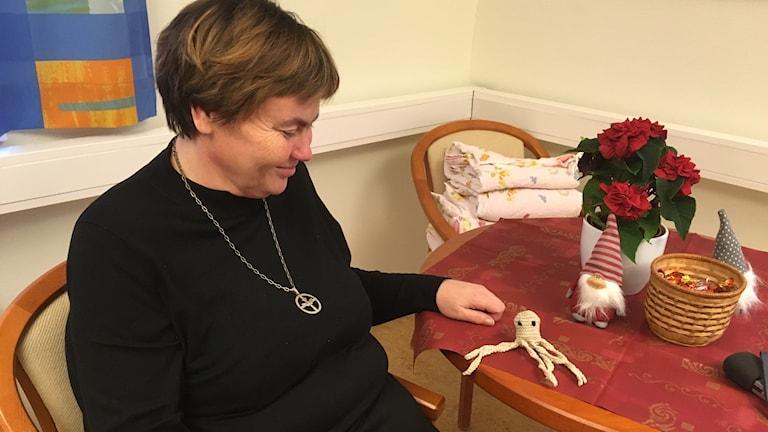 Diakoni Minna Hellström mustekala- turvalonkero pöydällään