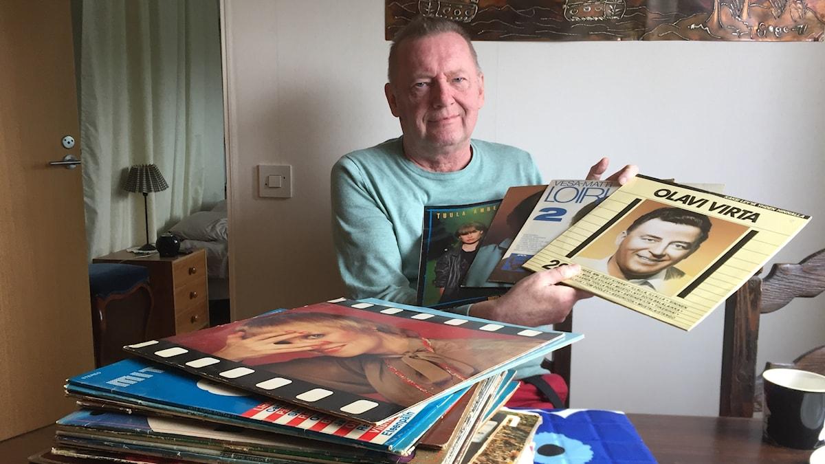 Jorma Rissanen pitelee kädessään levyjä, edessään iso pino levyjä.