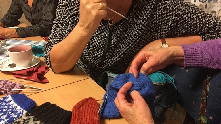 Käsityökerhossa vaihdetaan kokemuksia, villasukka tarkastelussa