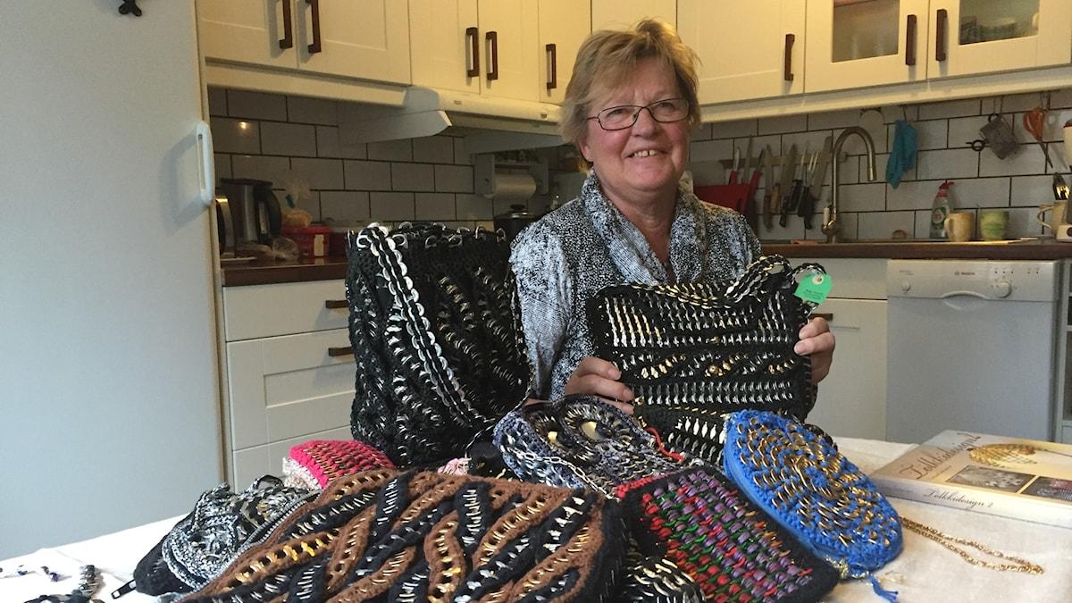 Maija Tolosen edessä pöydällä iso kasa laukkuja, jotka on tehty tölkkien avausnipsuista.