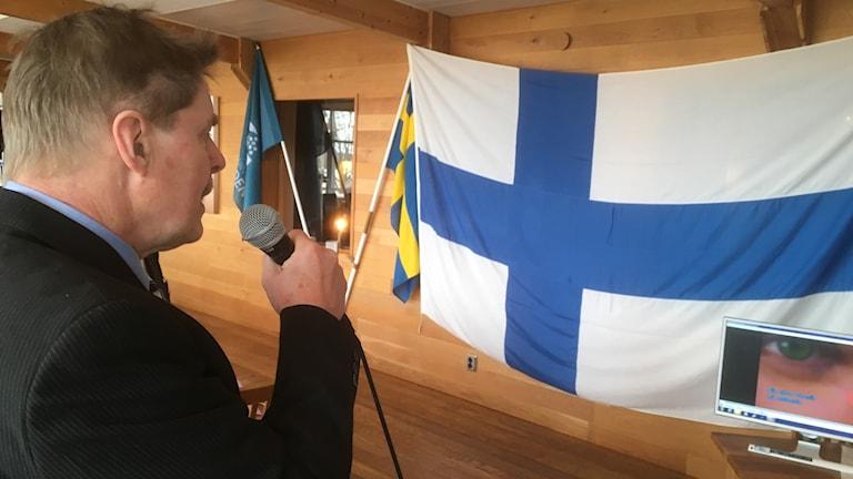 Lars Almén laulaa karaokea Suomen lippu taustalla