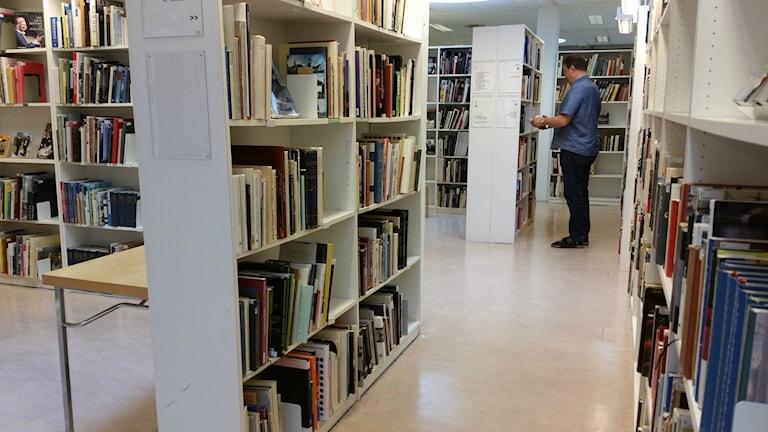 Kuvassa mies tutkii kirjaston hyllujen välissä kirjaa.