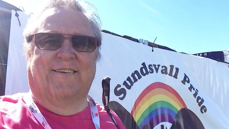 Sisuradion toimittaja Erpo Heinolainen Sundsvall Pride-festivaalijulisteen edessä. Foto: Sveriges Radio Sisuradio
