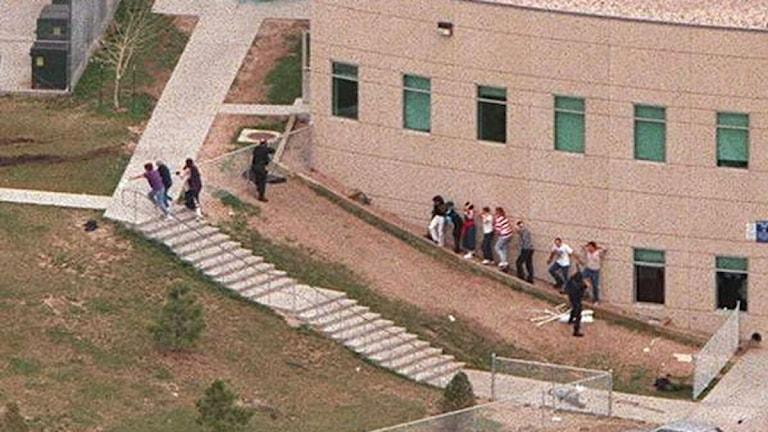 Columbine High school, Colorado i 20 april 1999. Elever och personal flyr för sina liv undan de tungt beväpnade gärningsmännen. Foto: Scanpix
