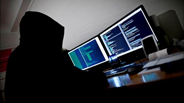 Person i svart huvudtröja lutar sig mot två monitorer fulla med text.