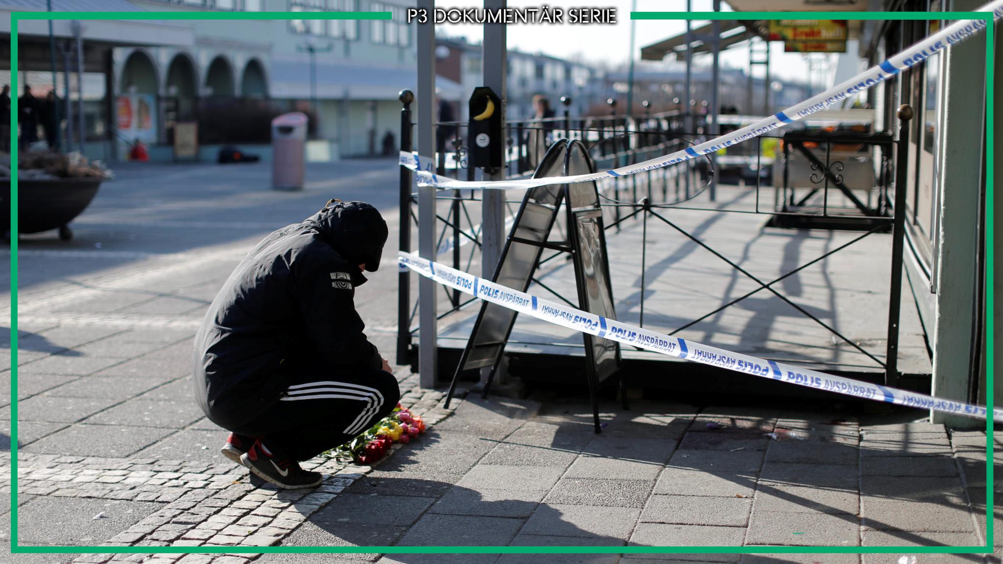 Kille hukar sig vid blommarna utanför avspärrningarna på Vår Krog & Bar