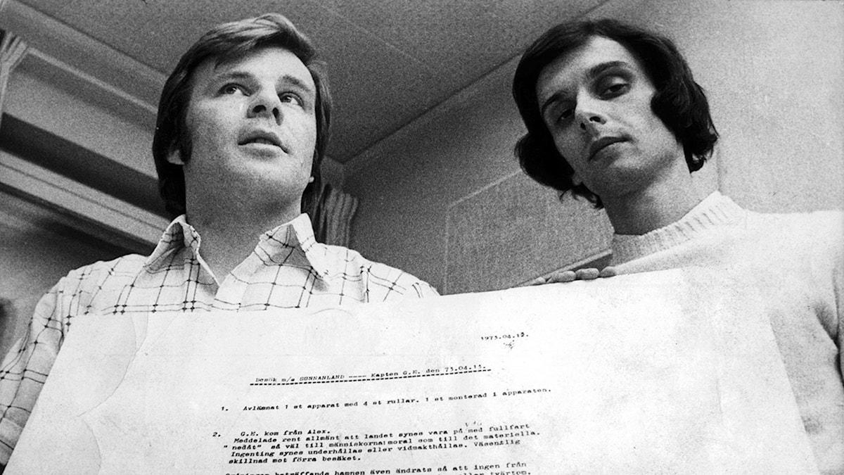 1973-05-15. Jan Guillou och journalistkollegan Peter Bratt. Guillou (t.v.) och Bratt, journalister på tidningen Folket i Bild/Kulturfront, ses här med ett uppförstorat dokument som visar hemliga underättelserapporter i samband med IB-afffären.