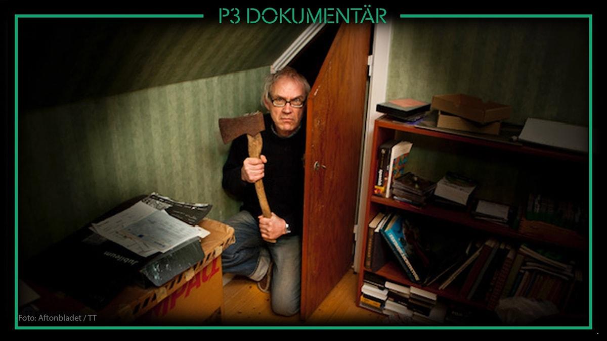 Foto av Lars Vilks som står på knä med yxa i handen