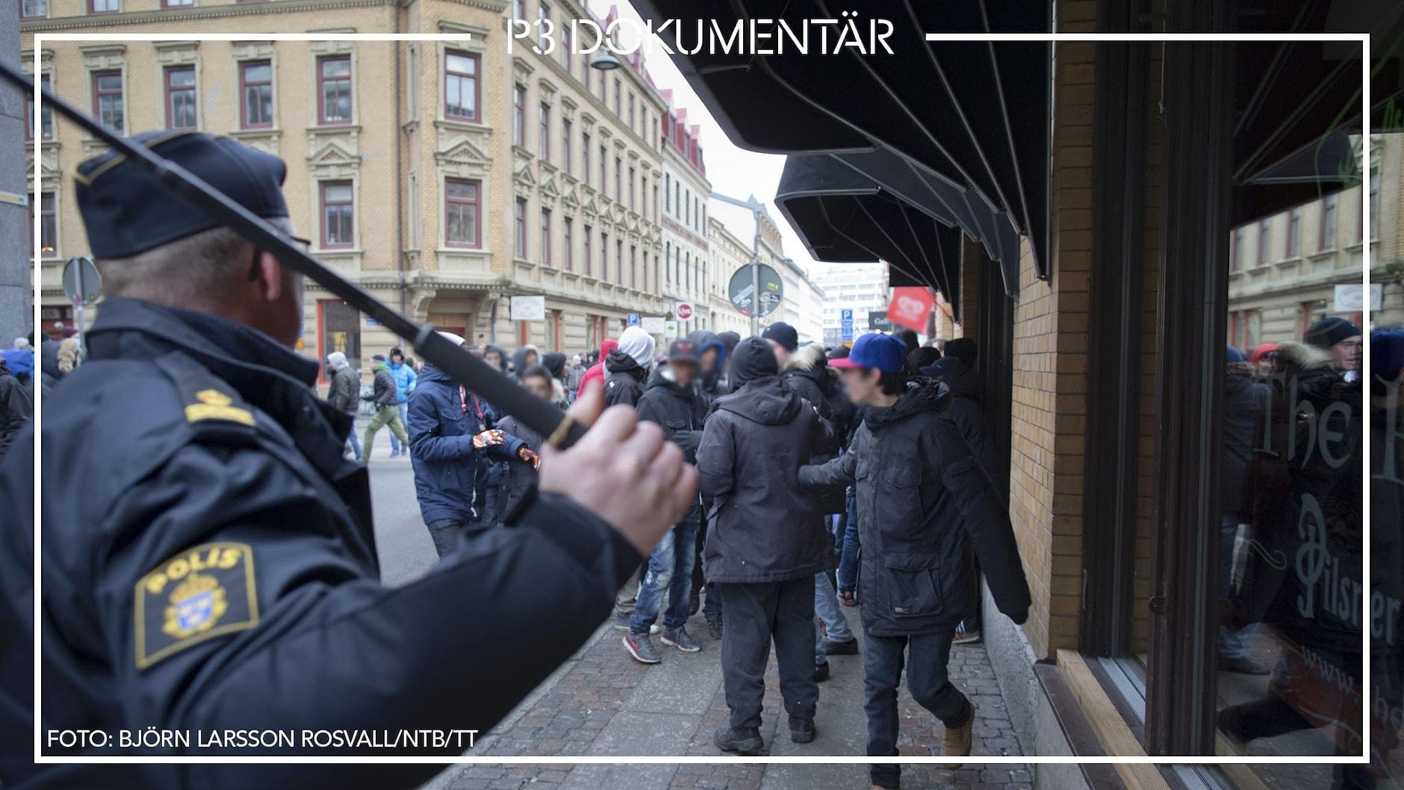En polis med höjd batong och en grupp ungdomar under Instagramupploppen i Göteborg.