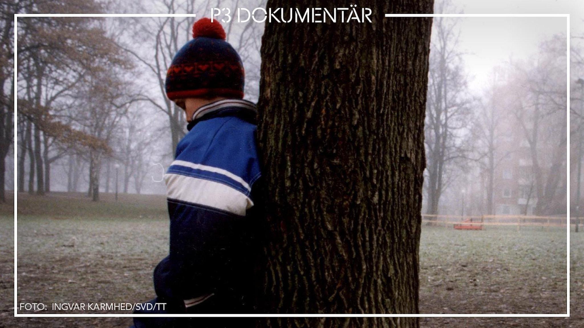 Ett barn står med ryggen mot ett träd, verkar ledsen. Det är dimma runt omkring.