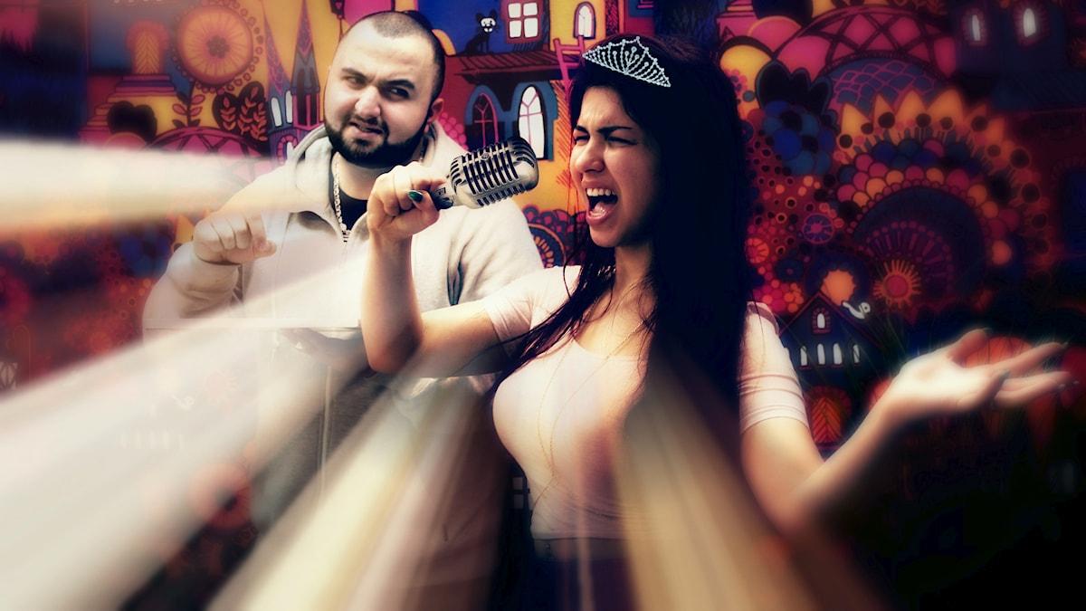 Mona står i förgrunden och sjunger in i en mikrofon, medan Hamza står bakom oförstående. Foto: SR