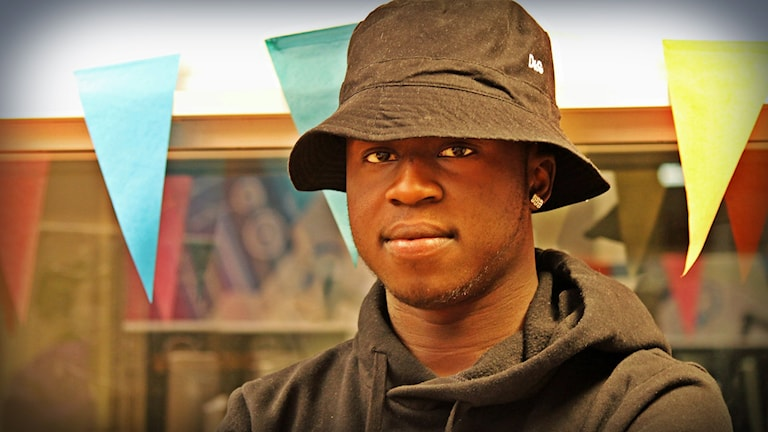 """Artisten """"Diamond"""" iklädd fiskarhatt och svart tröja poserar i Din Gatas studio med ett neutralt ansiktsuttryck. Foto: Suzan Arslan/SR"""
