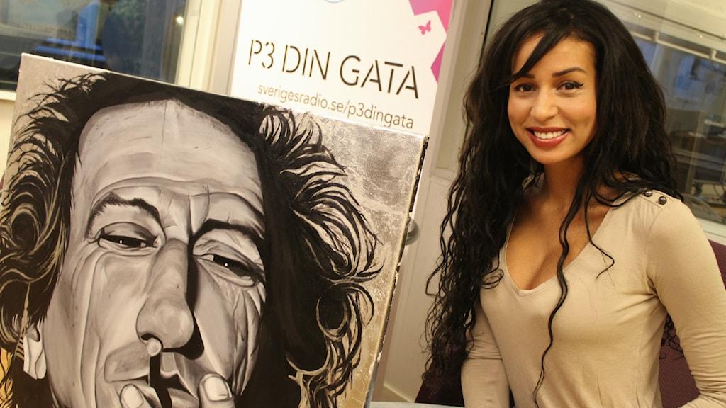 Bild på konstnären Rubia Caldeira och hennes tavla som förställer Keith Richards. Foto: Juan Havana/SR