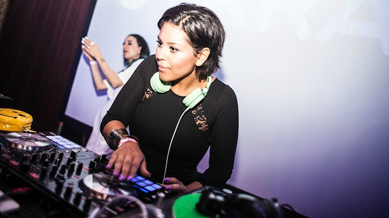 DJ Cleva, ung tjej med mörkt hår & svarta kläder, står bakom skivspelarna.