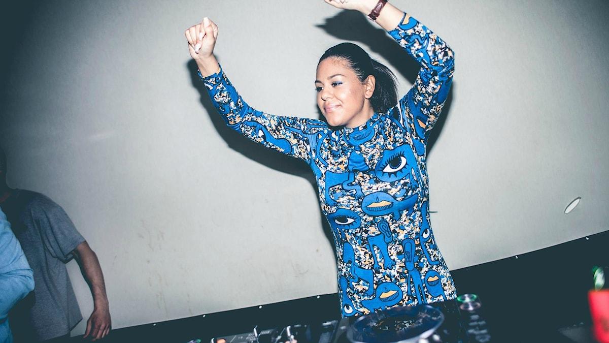 DJ Cleva, tjej med mörkt uppsatt hår och långärmad blåmönstrad klänning, står bakom skivspelarna med händerna i luften.