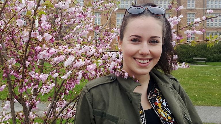 Bild på Linnea Visst som står framför en buske med rosa körsbärsblommor. Hon ser väldigt glad ut.
