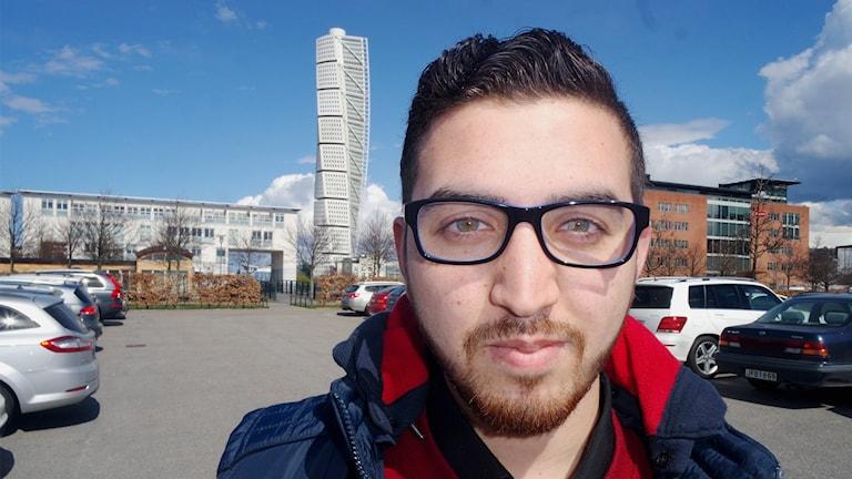 Bild på Ameen Al Katheeb som tittar in i Kameran. Turning Torso syns i bakgrunden.