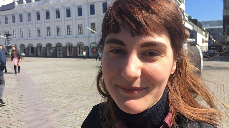 Bild på Linnea Samuelsson. Hon står på Gustav Adolfs Torg och tittar in i kameran och ler