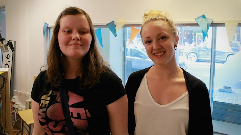 Bild på Emma Rävås och Agnes Tuneld som står i P3 Din Gatas studio och ler, och tittar in i kameran.