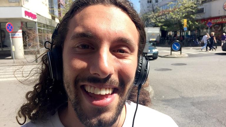 Alexander Nazar, med hörlurar på huvudet, tittar in i kameran och ler stort