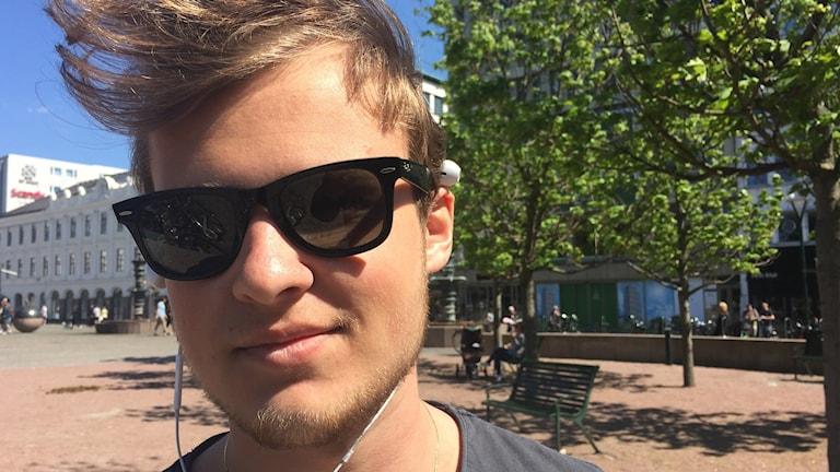 Mikael Nord har solbrillor och står på Gustav Afolfs Torg.