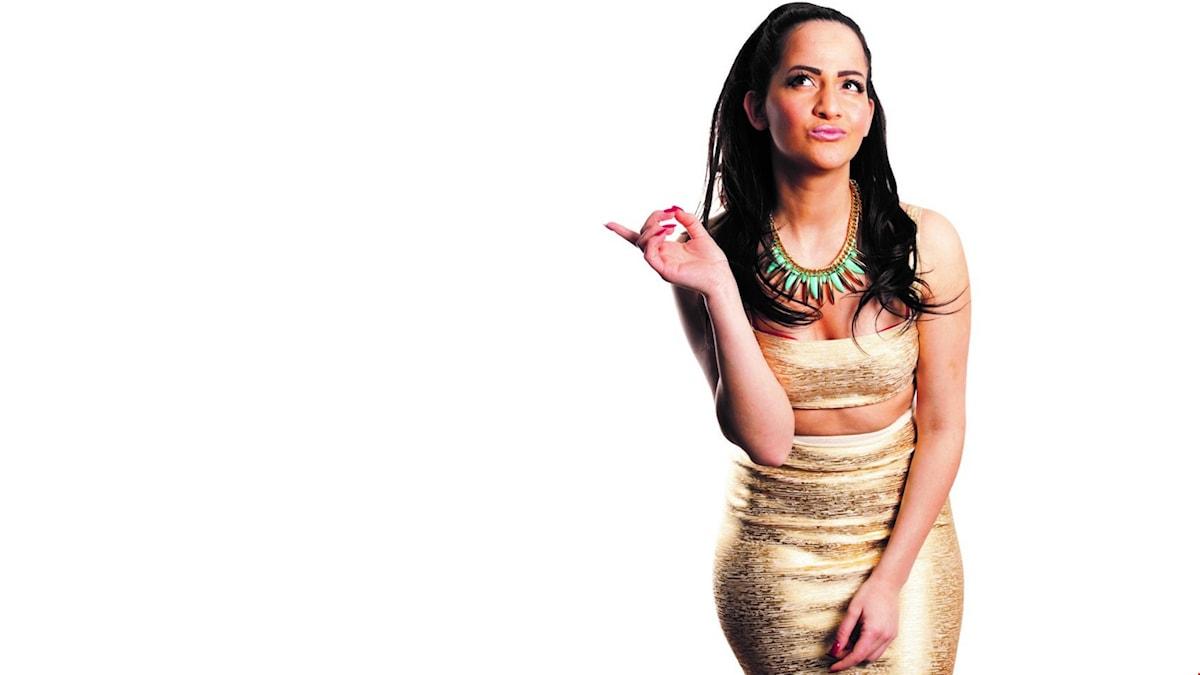 Suuz, mörkhårig tjej i guldiga kläder pekar till höger.