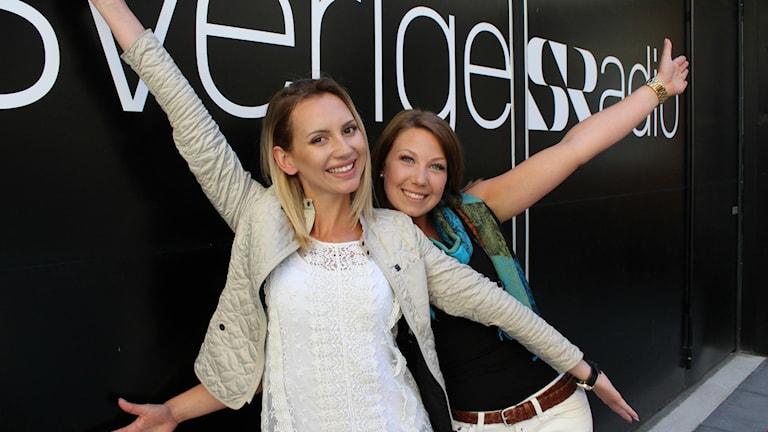 Bild på Pamela och Jeanette som står framför dörrarna till Sveriges Radio-huset. De ler och sträcker upp armarna i luften och ser pepp ut.