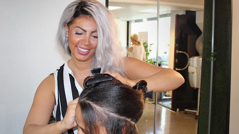 Bild på frisören Chantelle i en frisörsalong. Hon håller på och klipper en kvinna med brunt hår.