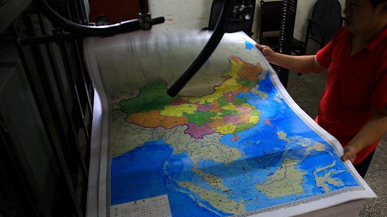 En man håller i en karta som visar Kina. Foto: TT.
