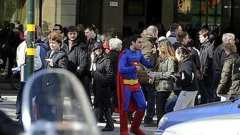 Stålmannen hjälper människor över gatan i Stockholm.