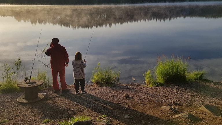 Förälder och barn vid brynet av Hubå-Långsjön i Hofors, redo med fiskespön.  Dimma över sjön och skog på andra sidan.