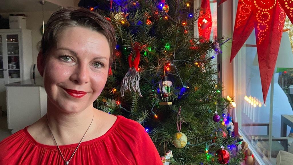 Maria Svemark står vid en julgran