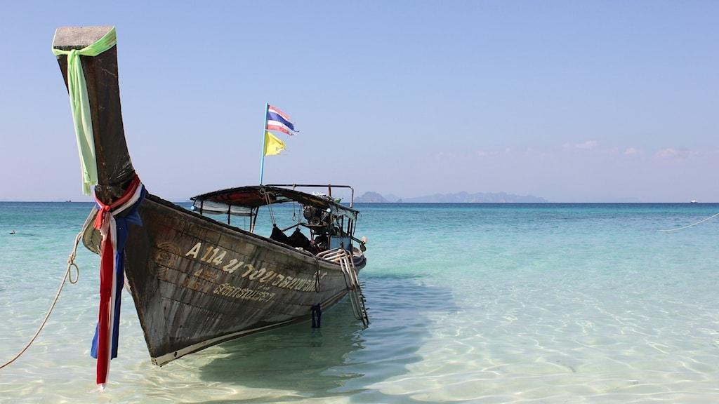 Thailand, strand, båt med longtail-båt thailändsk flagga i aktern.