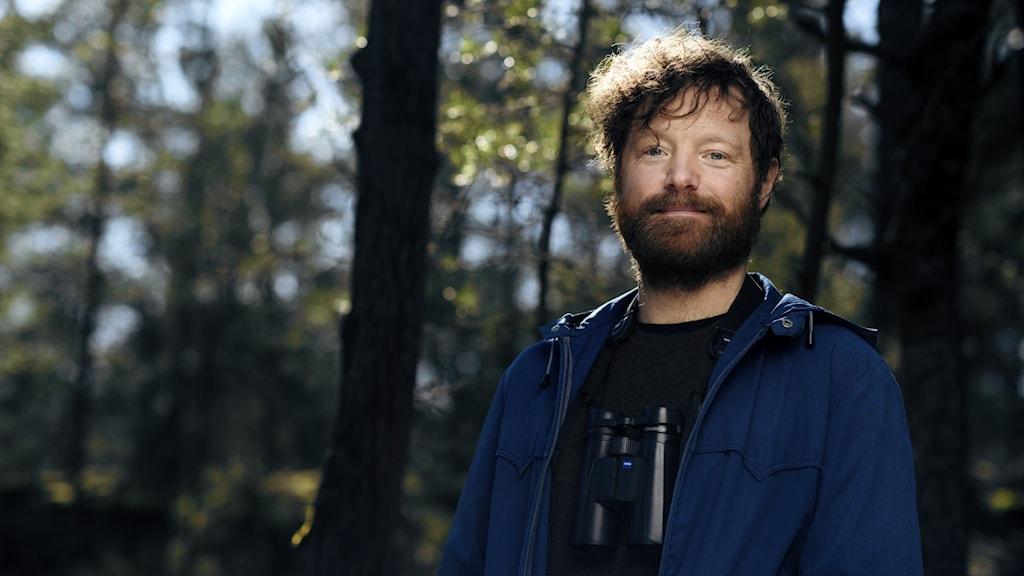 Författaren och Journalisten Erik Hansson ute i naturen i en blå jacka med träd i bakgrunden.