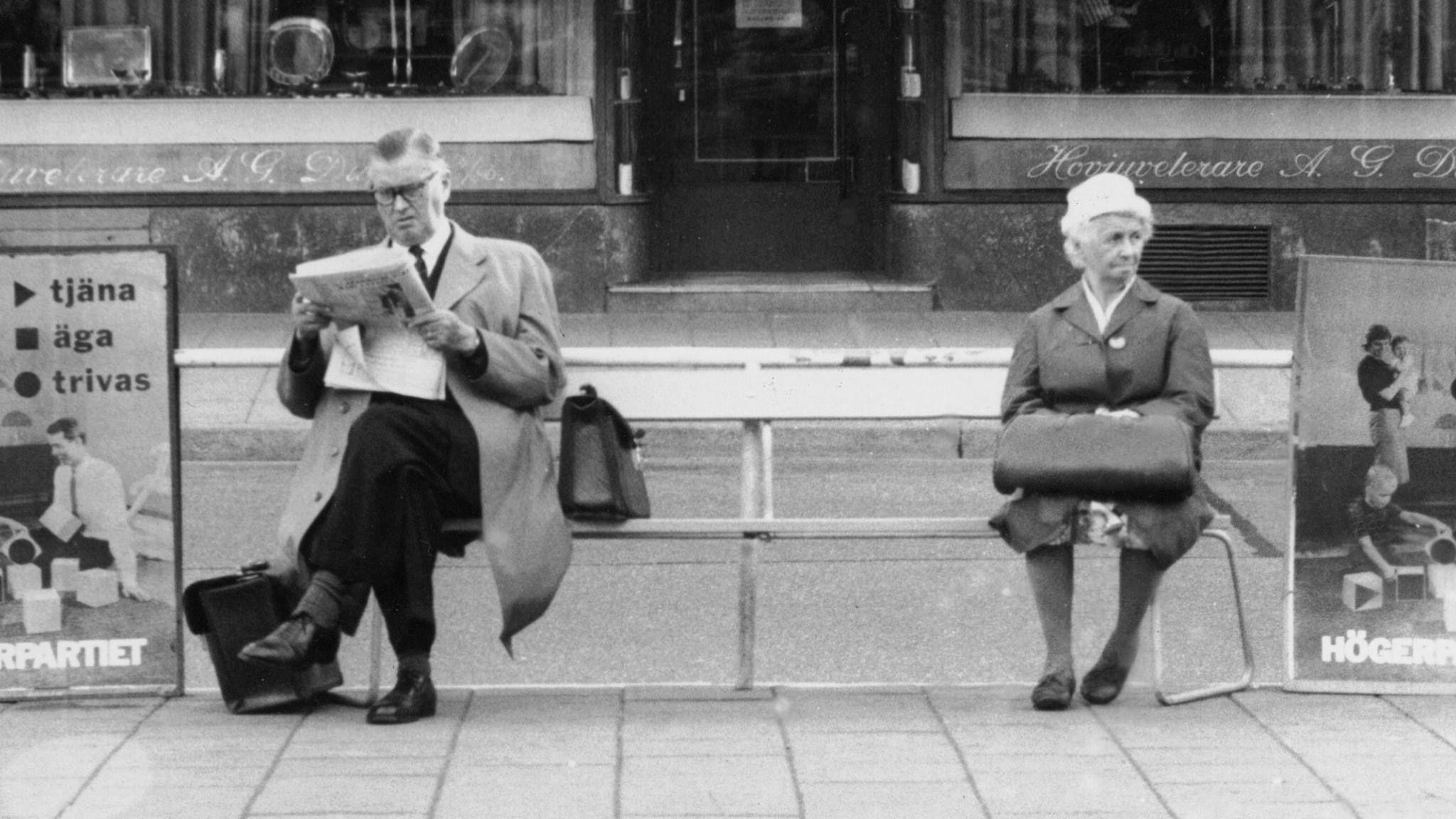 Svartvit arkivbild på två personer som väntar på en bänk.