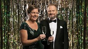 Lena och Karsten skålar framför glitterdraperi