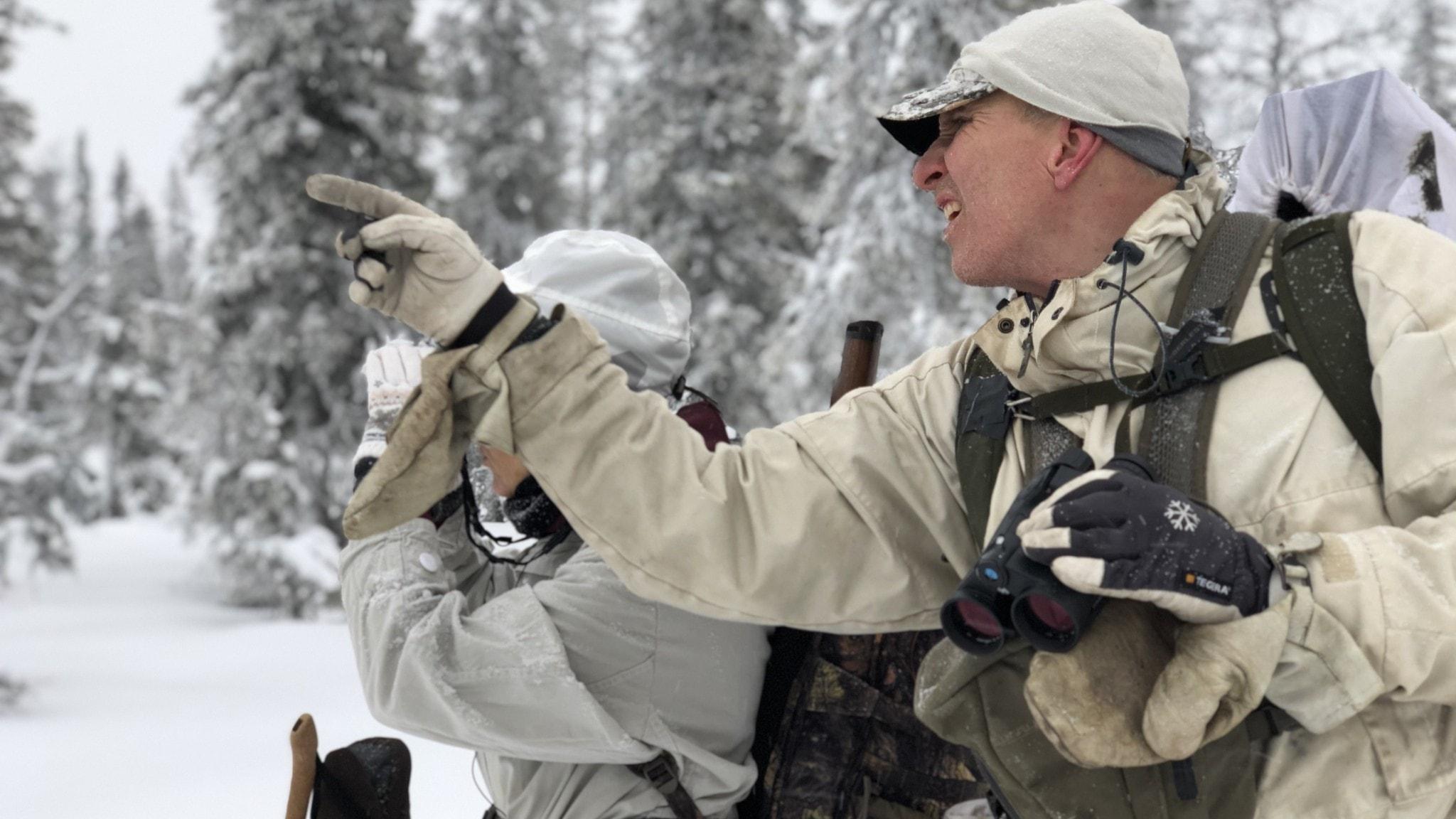 Niklas Lundberg, med snövita kläder på sig, jagar fågel och pekar upp i en topp.