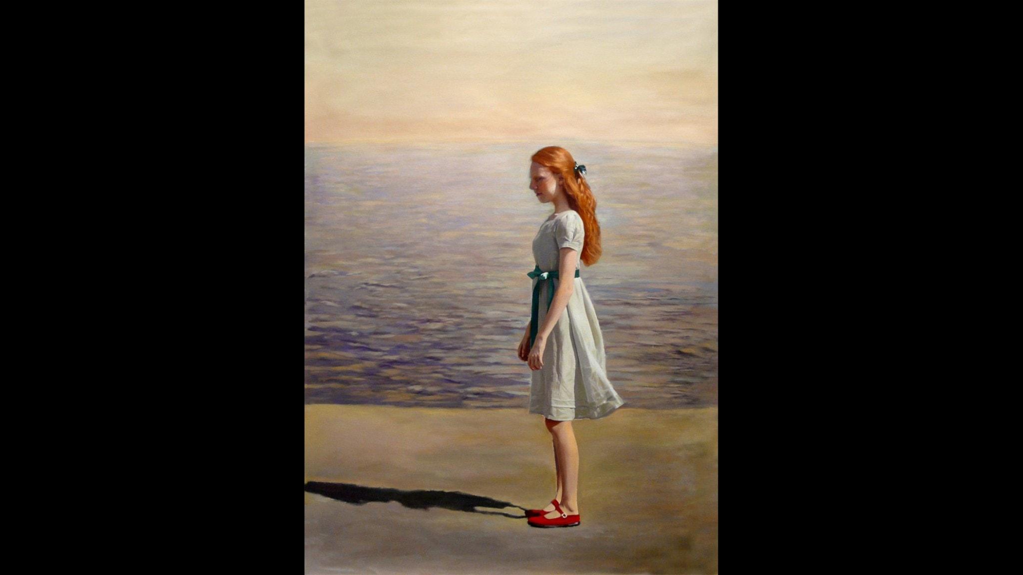Flicka vid vatten i blå klänning och rött hår