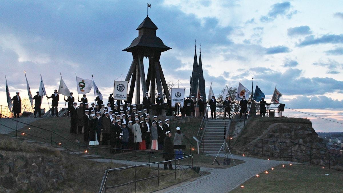 Uppsalastudenternas fanborg och kören Allmänna Sången vid Gunillaklockan utanför Uppsala slott.