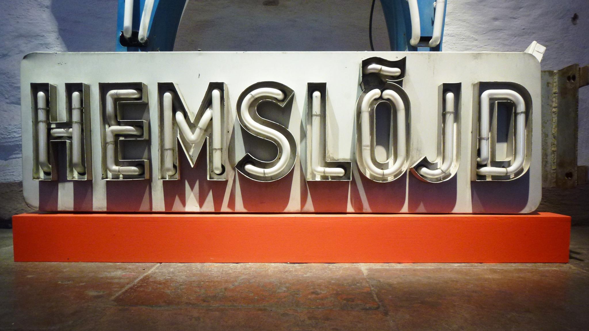 """""""Hemslöjd"""" skylt på Stockholms stadsmuseum, ursprungligen fanns den utanför butiken för Föreningen för Svensk Hemslöjd på Kungsgatan i Stockholm."""