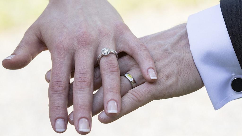 Händer med vigselringar, en kvinna och en man.