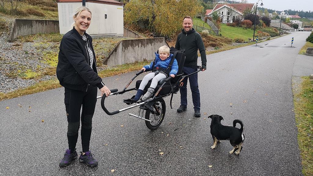 Hampus och hans föräldrar är ute på promenad med Hampus specialvagn.