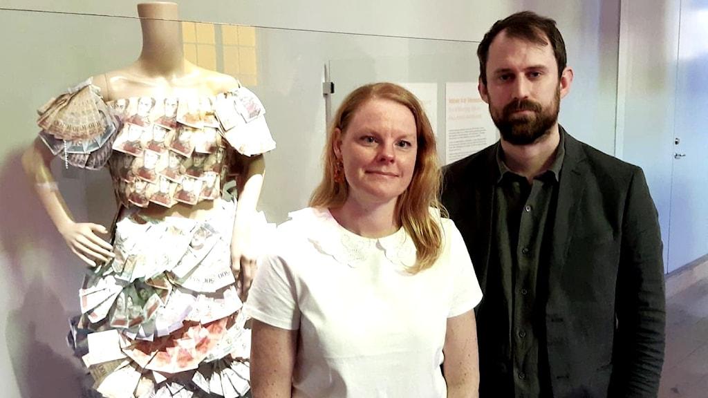 Sara Carlin och Martin Tunefalk framför en klänning gjord av värdelösa sedlar på Ekonomiska Museet