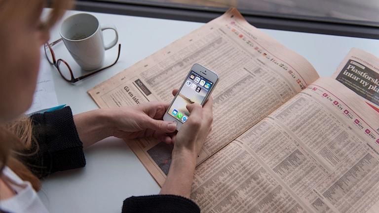 Kvinna med mobil och tidning.